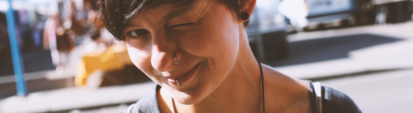Eine junge Frau mit schwarzen, kurzen Haaren blickt in die Kamera und kneift ihr linkes Auge zu.