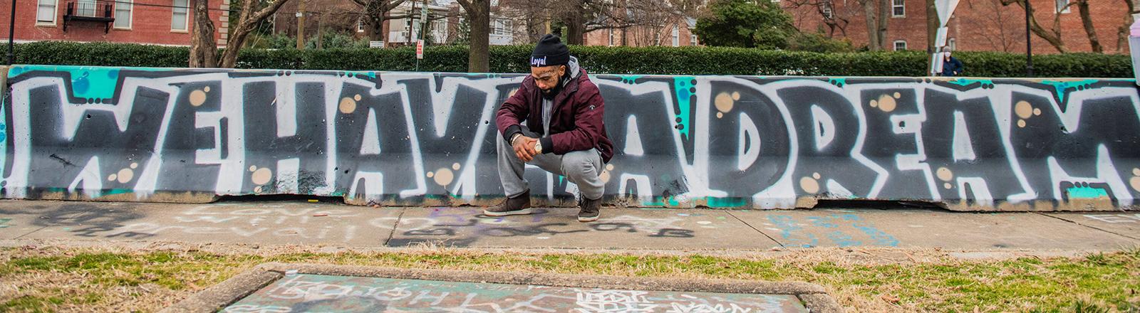 """In Richmond, USA sitzt ein junger Schwarzer vor dem Graffito: """"We have a Dream"""" (18.01.2021)"""