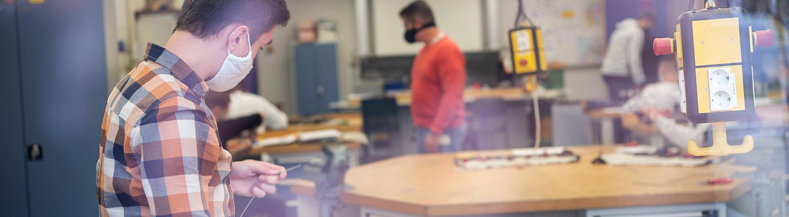 Auszubildende arbeiten am Schraubstock in einer Berufsschule (30.10.2020)
