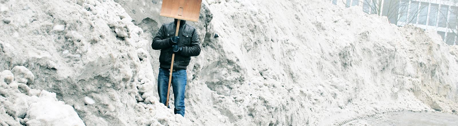 Ein Mann versteckt sein Gesicht hinter einer Schneeschippe; er steht vor einem riesigen Schneeberg in einer Stadt.