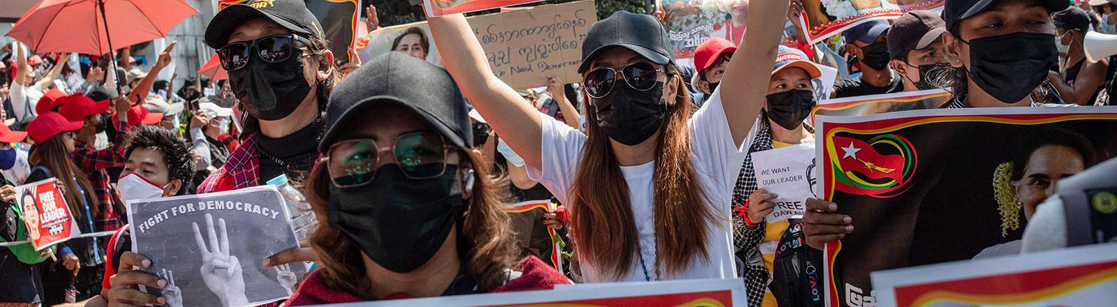 Bei Protesten in Yangon (Myanmar) halten Frauen Plakate mit dem Konterfei von Aung San Suu Kyi in die Luft. Sie ist nach einem Militärputsch in Haft (09.02.2021)