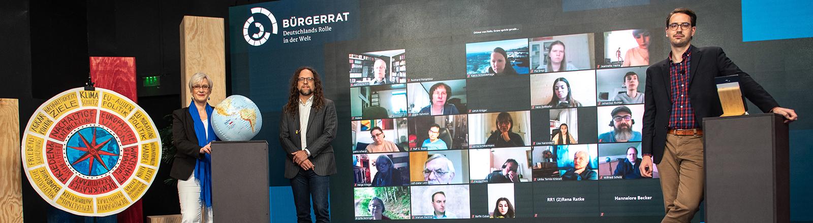 Der Bürgerrat lief digital ab. Auf einer Leinwand sind die Teilnehmenden einer Videokonferenz zu sehen. Davor stehen drei Menschen in einer Art Studio; sie haben den Bürgerrat moderiert und begleitet.