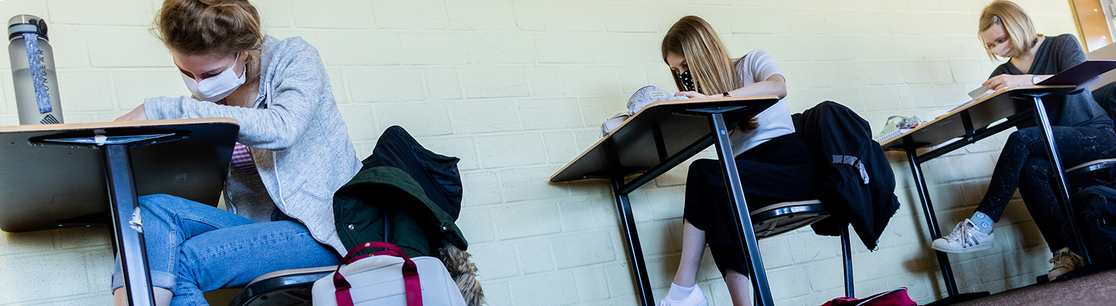Drei Schülerinnen sitzen an Einzeltischen und arbeiten; sie tragen Mund-Nase-Masken (23.04.2020); Foto: dpa