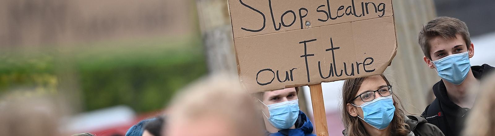 """Beim Klimastreiktag halten drei junge Erwachsene in Potsdam ein Schild hoch mit dem Spruch """"Stop Stealing our Future"""" (Hört auf, uns unsere Zukunft zu stehlen) (25.09.2020); Foto: dpa"""