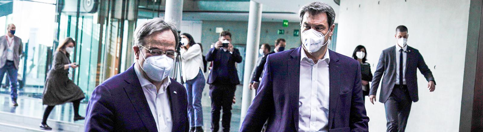 Armin Laschet und Markus Söder laufen gemeinsam zu einer Pressekonferenz im Paul-Loebe-Haus in Berlin (11.04.2021)