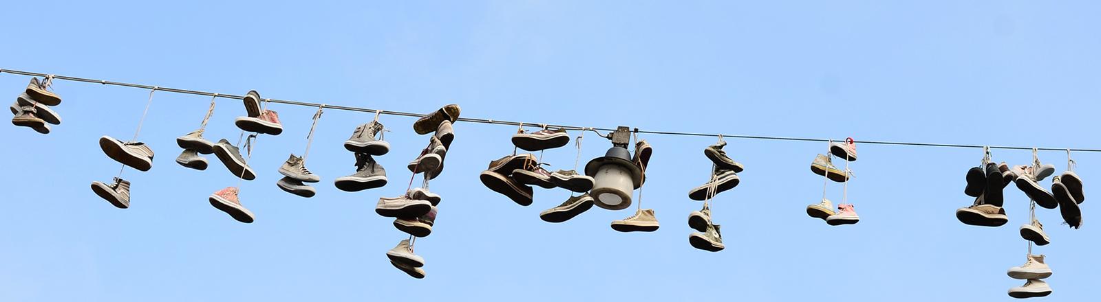 Alte Turnschuhe hängen mit den Schnürsenkeln über einem Kabel, an dem eine Straßenlampe hängt.