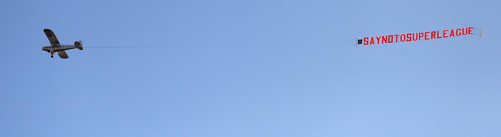 In Großbritannien fliegt ein Flugzeug vor blauem Himmel. Es zieht ein Banner hinter sich her, auf dem steht: Say No To Super League (19.04.2021)