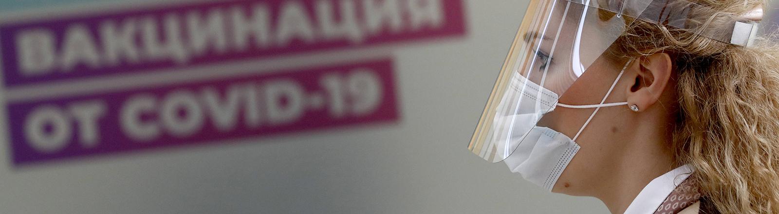 In einem Corona-Impfzentrum in Moskau steht eine Frau mit Mund-Nase-Schutz plus transparenten Gesichtsvisier (07.04.2021)