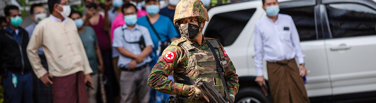 In Rangun, der Hauptstadt Myanmars, steht ein uniformierter Soldat mit Maschinengewehr vor einer Menschentraube (02.02.2021)