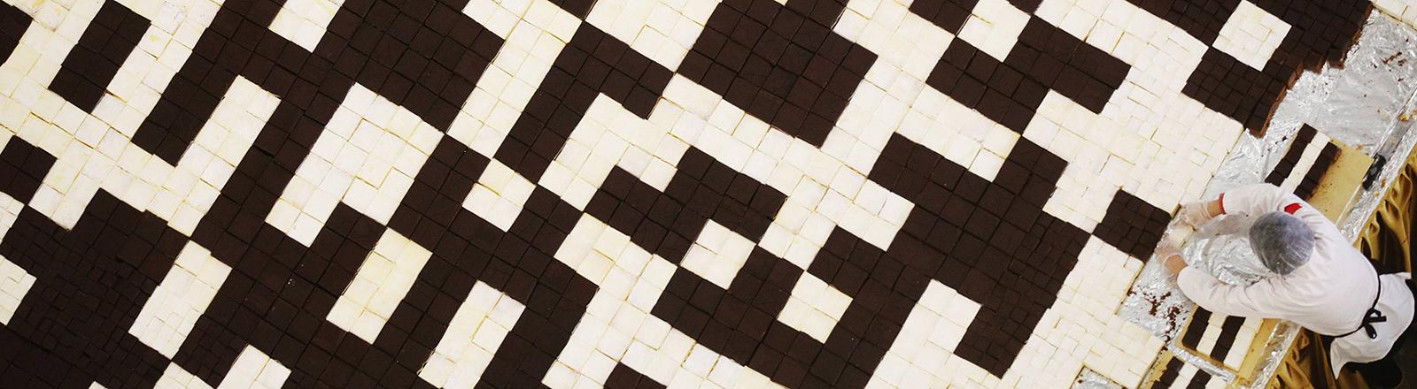 Aufnahme von oben: Ein großer Kuchen trägt auf der Oberfläche einen QR-Code. Eine Person steht am Rand und schneidet ein Stück ab.