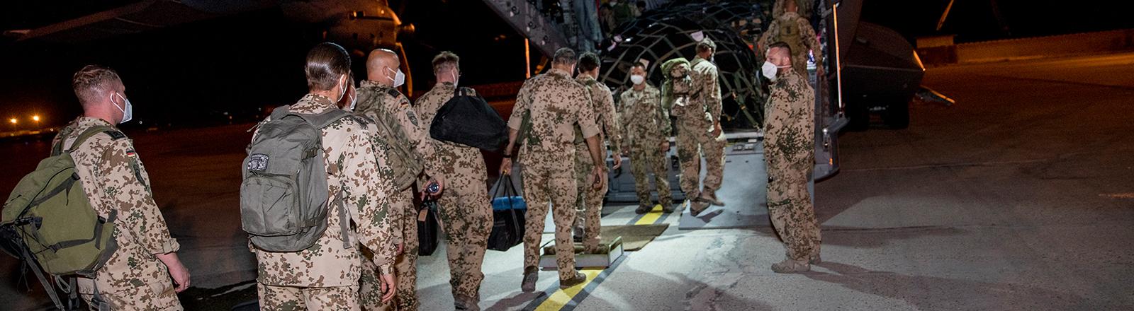 Soldaten der Bundeswehr steigen in Afghanistan in eine Transportflugzeug ein; sie tragen Rucksäcke und Taschen (27.06.2021)