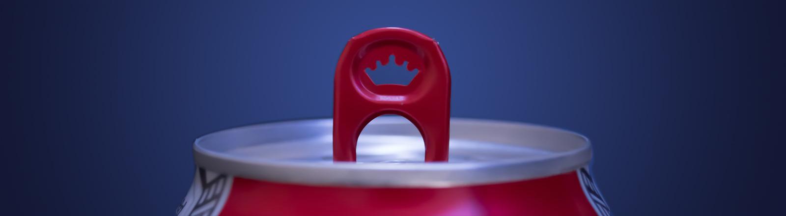 Der obere Teil einer roten Getränkedose aus Metall, die geöffnet ist. Der Hintergrund ist blau.
