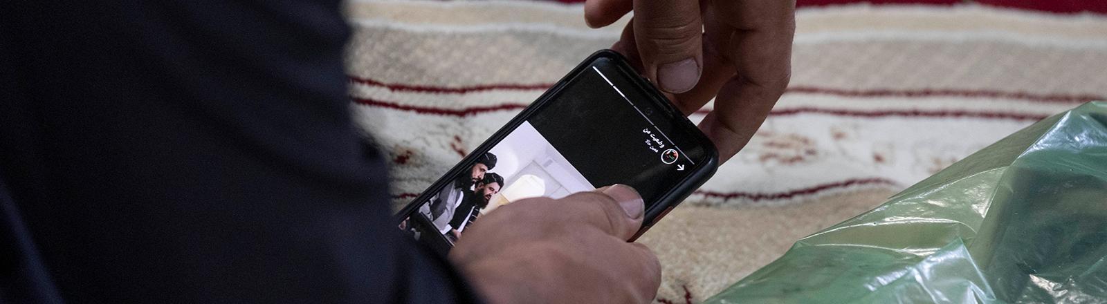 Ein Mann hält ein Smartphone in der Hand; es sind lediglich seine beiden Hände zu sehen. Auf dem Bildschirm des Handys sind Angehörige der Taliban zu sehen (21.08.2021)