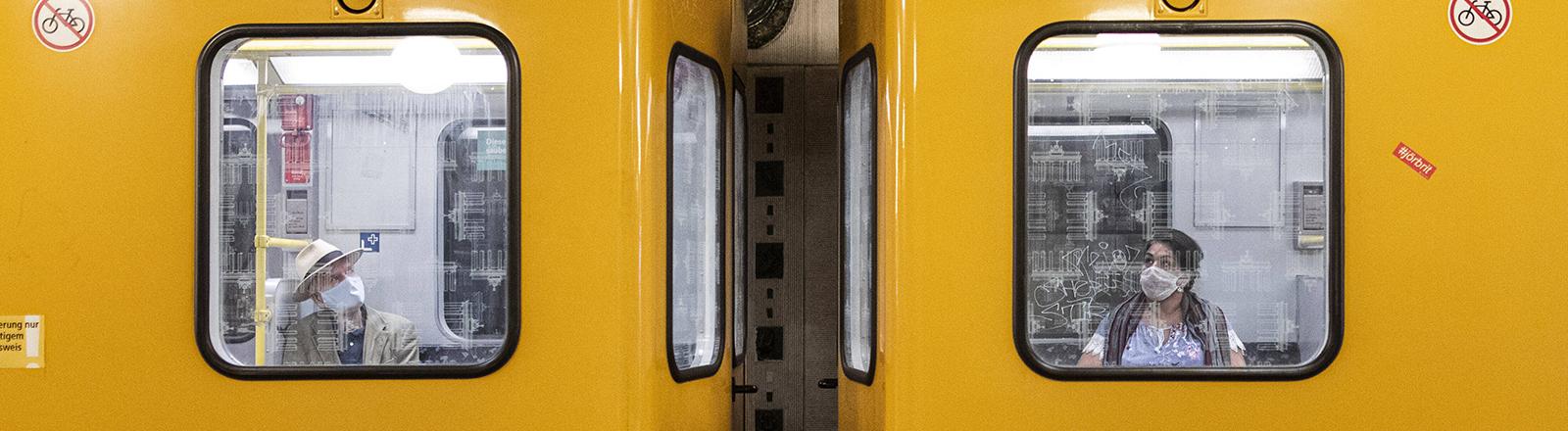 Zwei Waggons der Berliner U-Bahn. In beiden sitzt je ein Fahrgast mit Mund-Nase-Schutz.