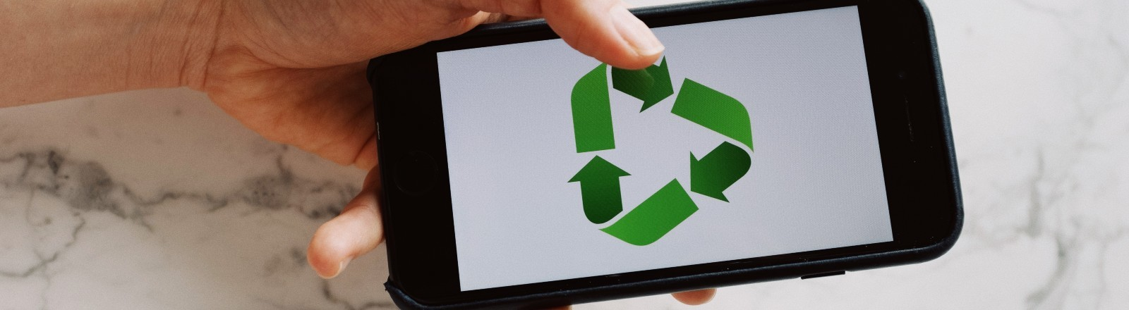 Jemand hält ein Smartphone in der Hand, auf dem ein Wiederverwertungs-Symbol gezeigt wird.