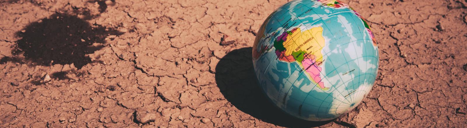 Ein Globus liegt auf trockener Erde.