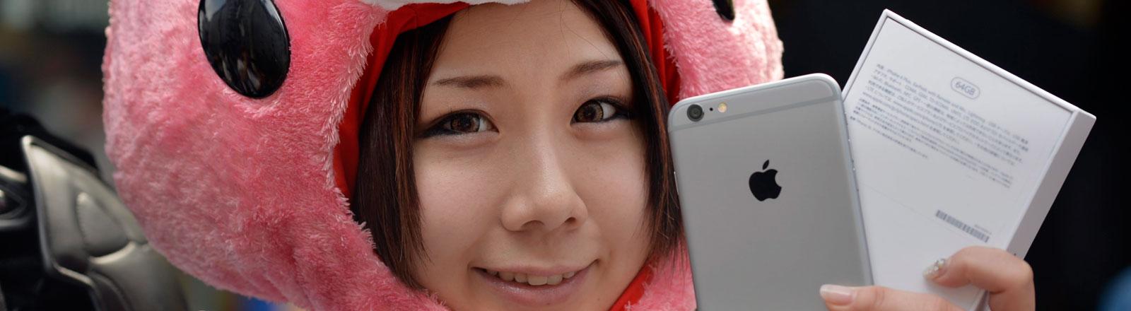 Eine Japanerin mit lustiger Kappe hält ein iPhone 6 in die Luft.