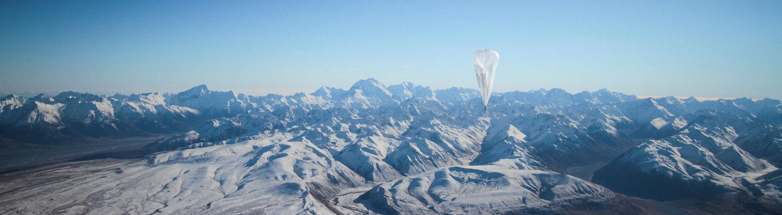 Ein Heliumballon von Google am Himmel über einem Gebirge. Der Ballon soll ein Internetsignal auf die Erde bringen.