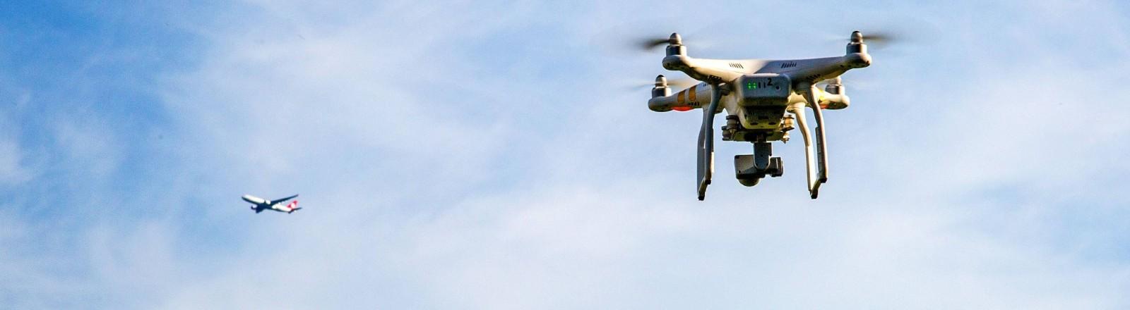 Eine Drohne folgt einem startenden Flugzeug am Flughafen Düsseldorf.