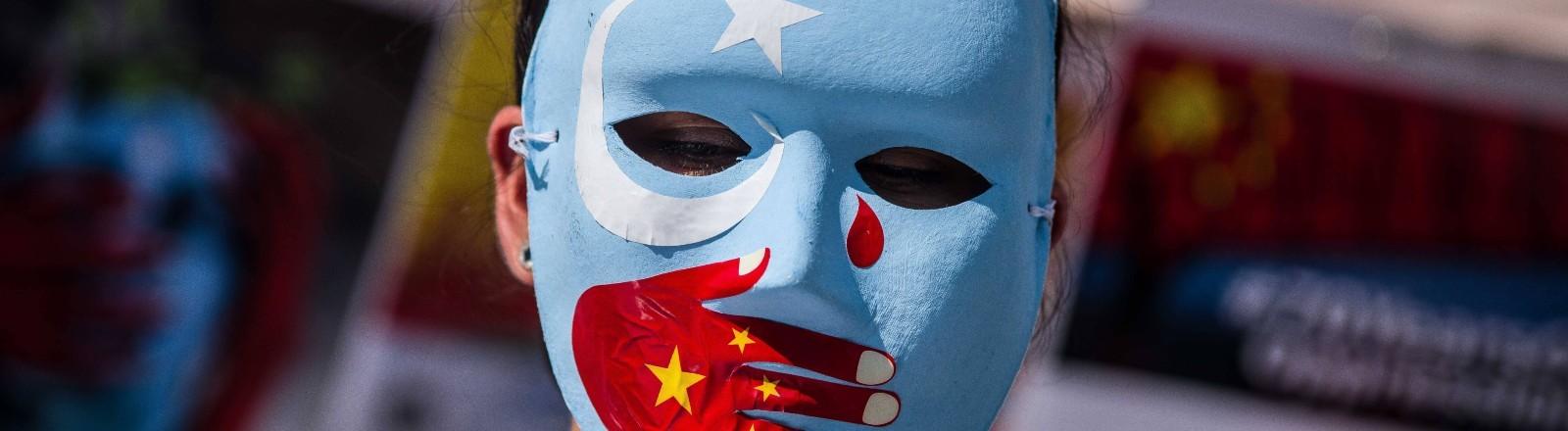 Eine Person trägt eine Maske, auf der die Flagge der uigurischen Unabhängigkeitsbewegung zu sehen ist und die chinesische Flagge.
