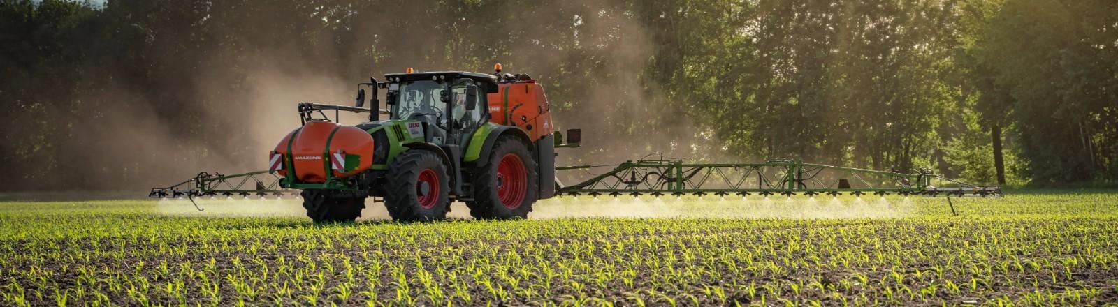 Traktor fährt über ein Feld und versprüht Pflanzenschutzmittel