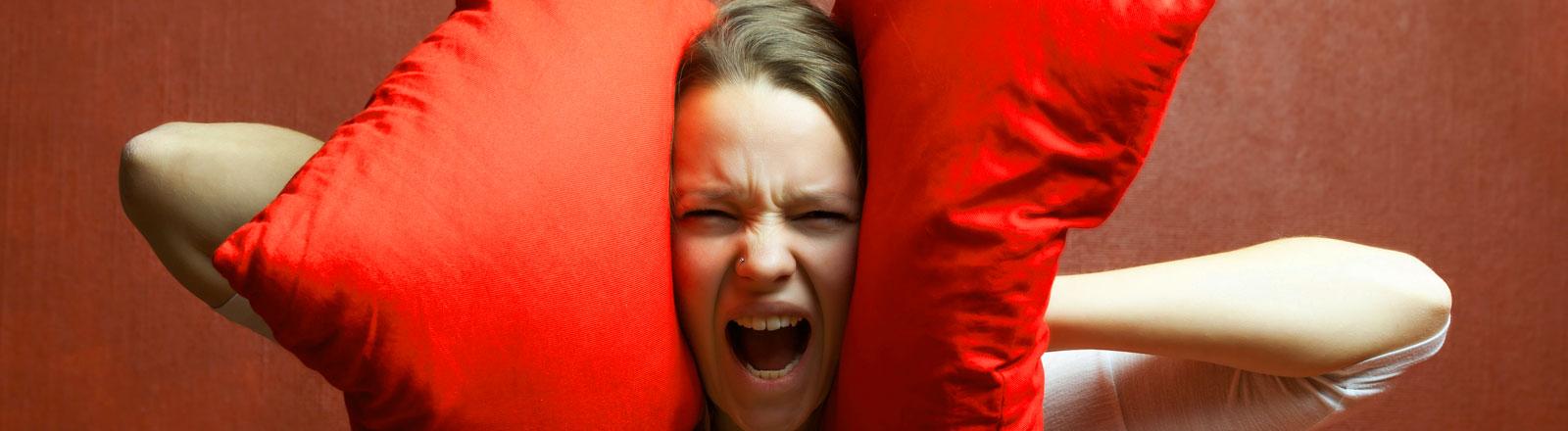 Eine Frau hält sich zwei Kissen an den Kopf