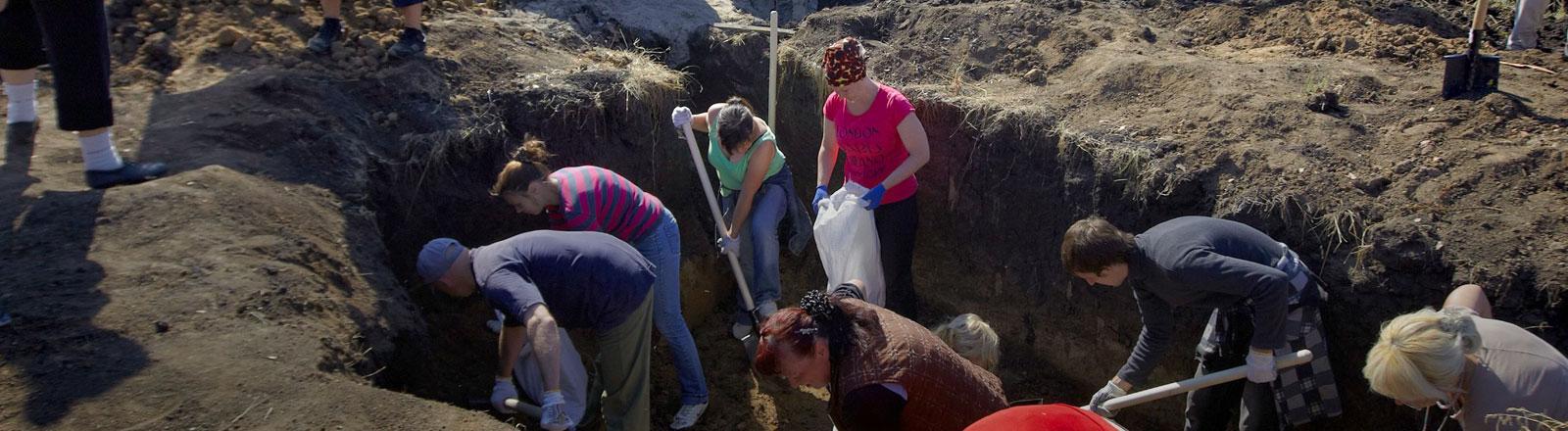 Freiwillige aus der Ukraine graben ein Loch für die Mauer, die zwischen der Ukraine und Russland errichtet werden soll.