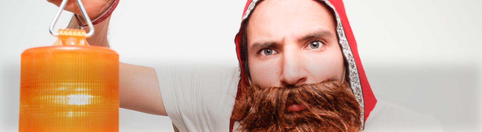 Ein Mann mit Bart hält eine Lampe hoch.