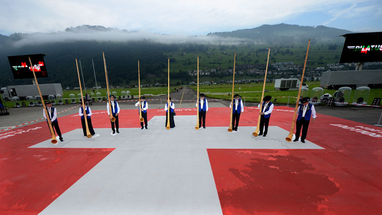 Alphorn blowers stand on a huge Swiss flag during a rehearsal prior to the rollout of the new Pilatus PC-24, a twin-engine business jet development by Pilatus Aircraft in Stans, Switzerland, 01 August 2014.