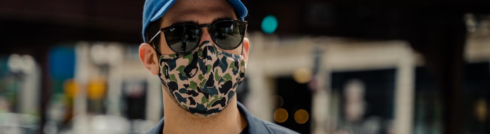 Mann trägt Sonnenbrille und Maske