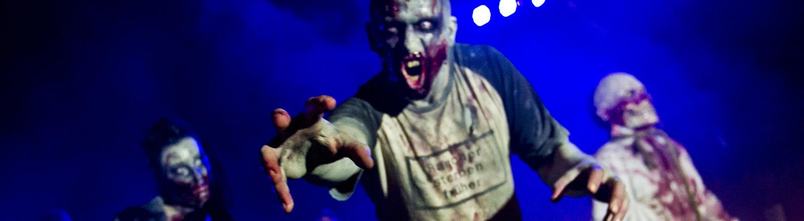 Als Zombies verkleidete Menschen greifen nach dem Betrachter.
