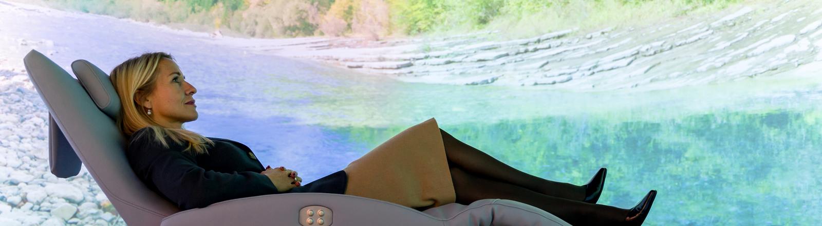 Frau in einem Relax Sessel vor Naturpanorama im Wellnessstudio Anima Mentis in Wien