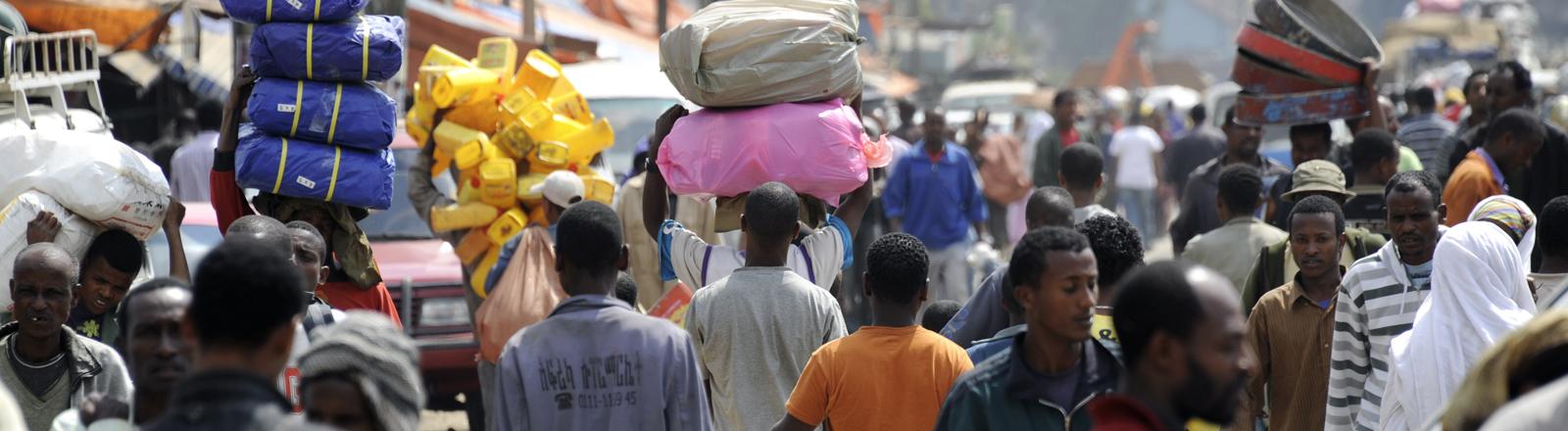 Menschen tragen am Donnerstag (13.01.2011) in Addis Abeba in Äthiopien am Mercato, dem großen Markt, Waren auf ihren Köpfen.
