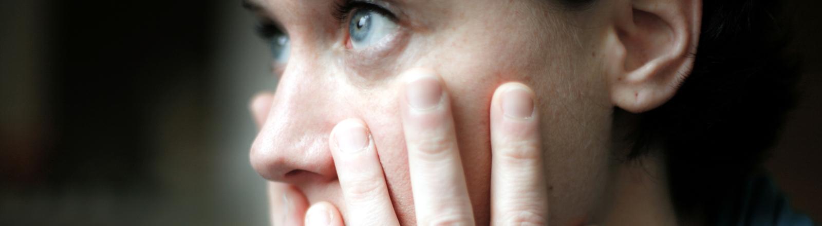 Ein Frau mit Händen vor dem Gesicht