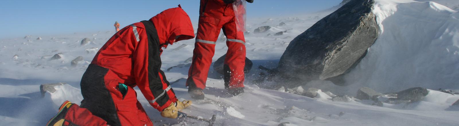 Zwei Geowissenschaftler entnehmen am 25.01.2012 an einer der letzten Gletschermoränen vor dem Polarplateau im südwestlichen Sør Rondane in der Antarktis Gletschereis für spätere Analyse im Labor.