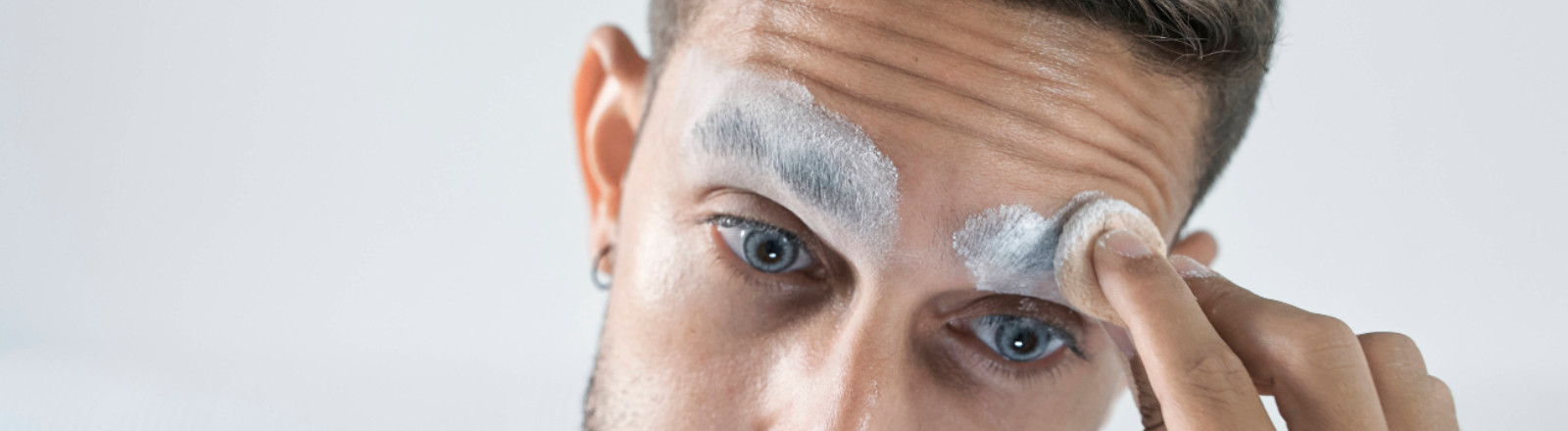 Mid adult man applying face powder on eyebrow in front of mirror