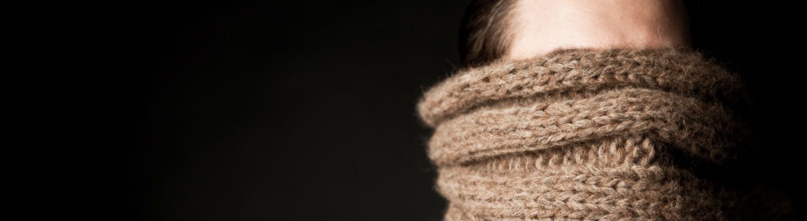 Ein Mann mit einem braunen Schal vorm Gesicht.