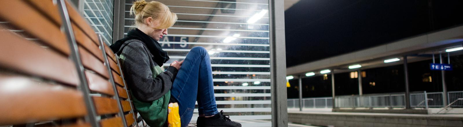 Eine junge Frau wartet am späten Abend vom 06.11.2014 am Bahnhof in Hildesheim (Niedersachsen) auf einen Zug.
