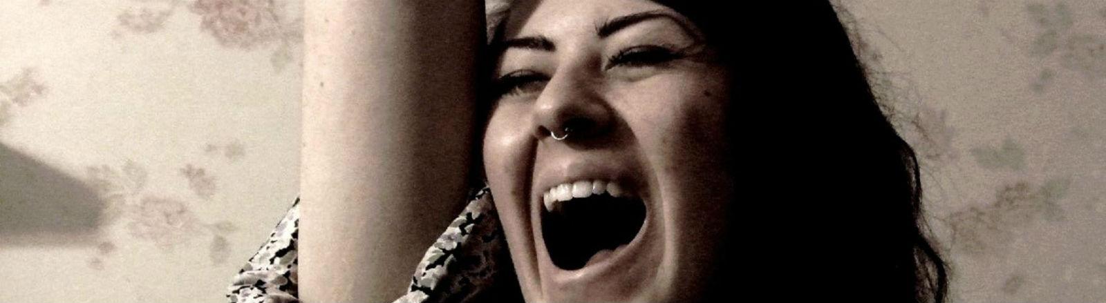 Eine junge Frau singt mit offenem Mund.