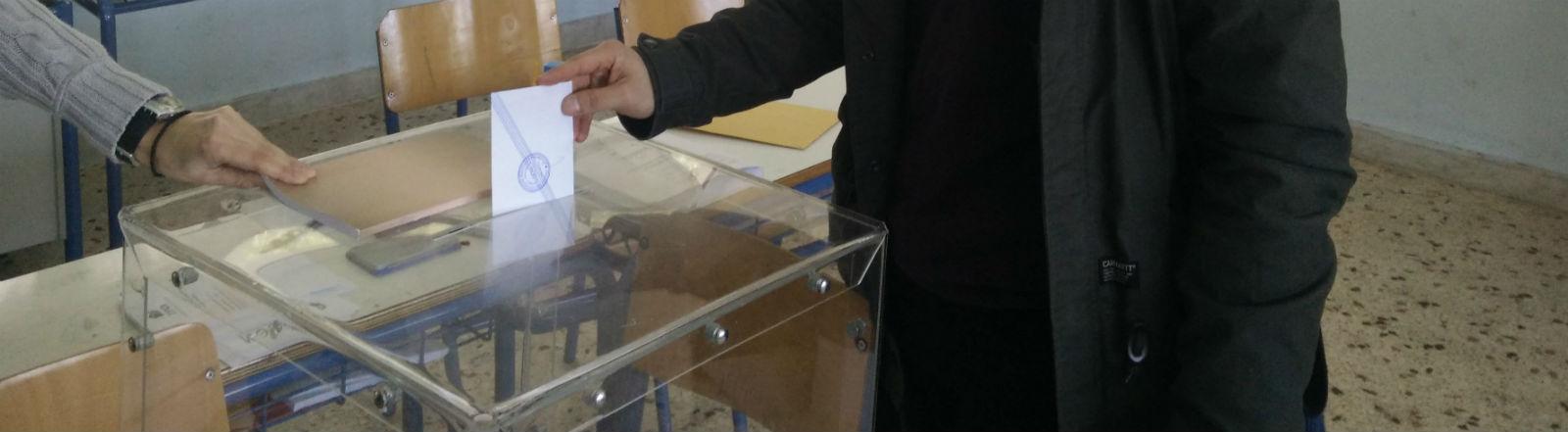 Ein junger Mann wirft einen Umschlag in eine Wahlurne.