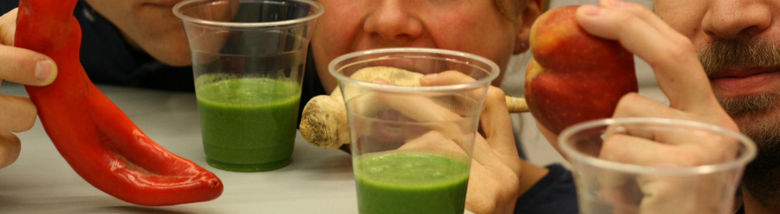 Drei Menschen halten krummes Gemüse, vor sich drei grüne Smoothies.