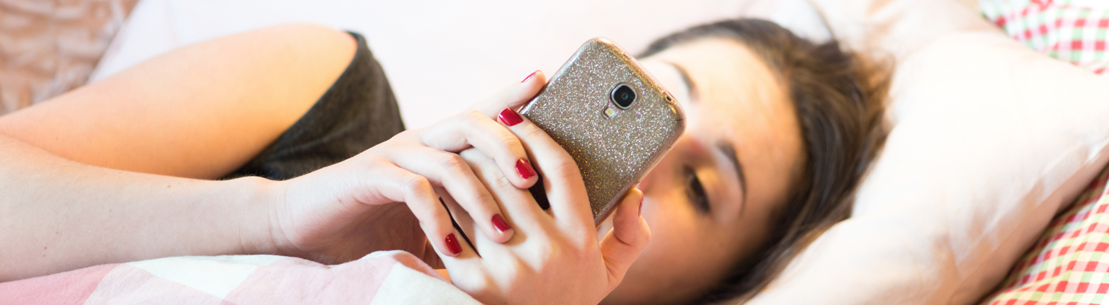 Ein junge Frau mit Smartphone im Bett