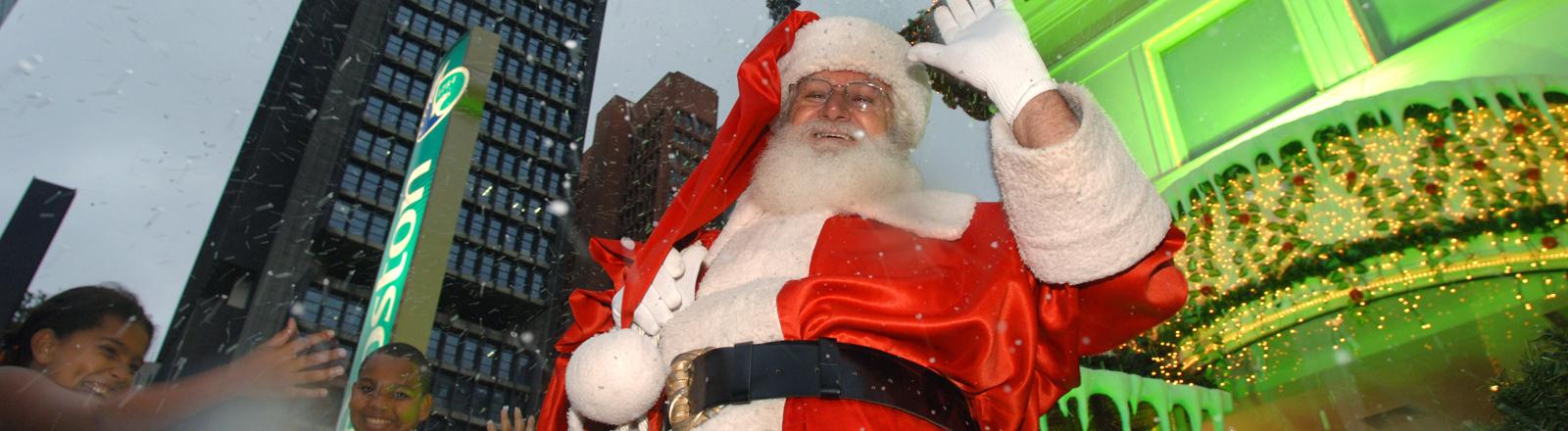 """Der Weihnachtsmann """"Papa Noel"""" winkt am Samstag (10.12.2005) vor der beleuchteten Skyline der Avenida Paulista im Zentrum der brasilianischen Wirtschaftsmetropole Sao Paulo in die Kamera, Kinder jubeln dem Weinachtsmann begeistert zu."""