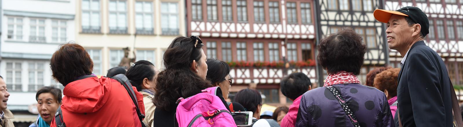 Ein Gruppe chinesischer Touristen besichtigt am 23.06.2015 den Römerberg in Frankfurt am Main (Hessen) mit seinen Fachwerkhäusern.