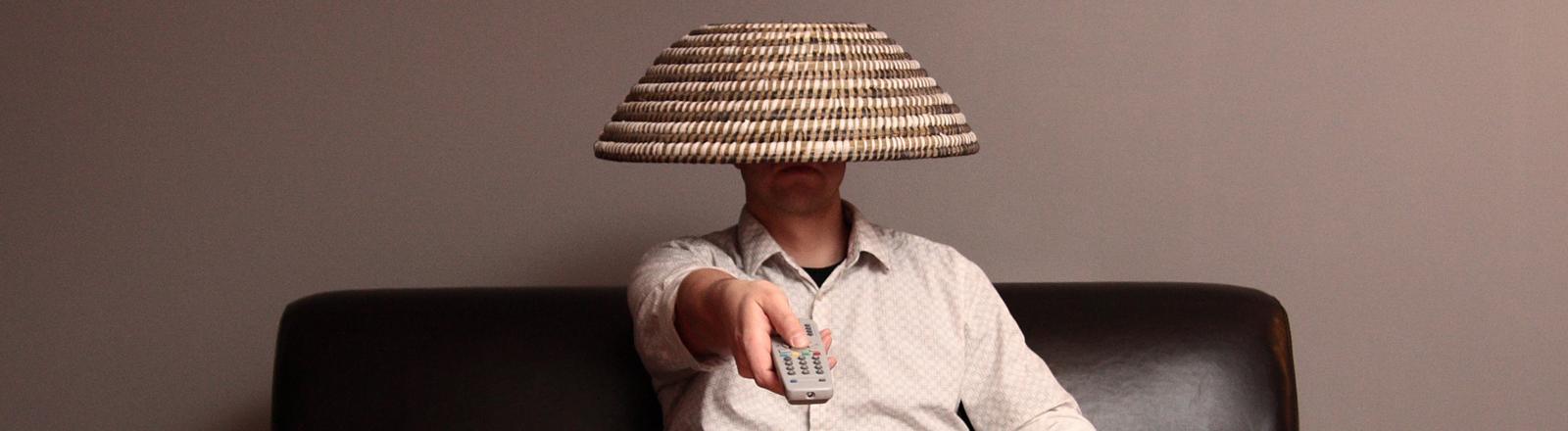Ein Mann mit einer Fernbedienung auf einem Sofa