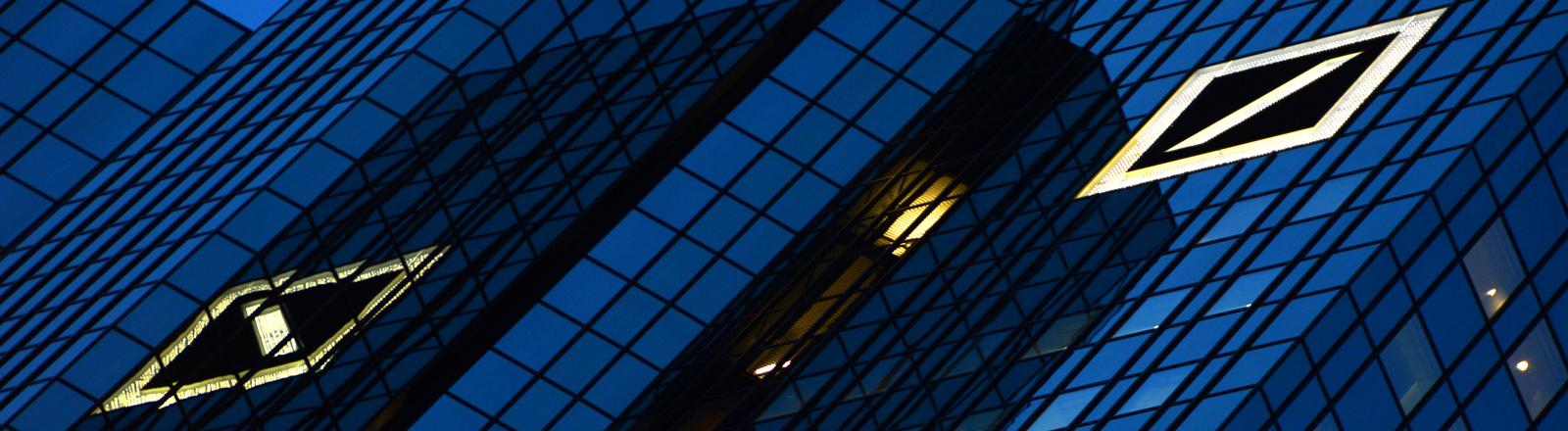 Das Logo der Deutschen Bank leuchtet am 08.01.2014 im Abendlicht auf der Fassade des größten deutschen Geldinstituts in Frankfurt am Main (Hessen).