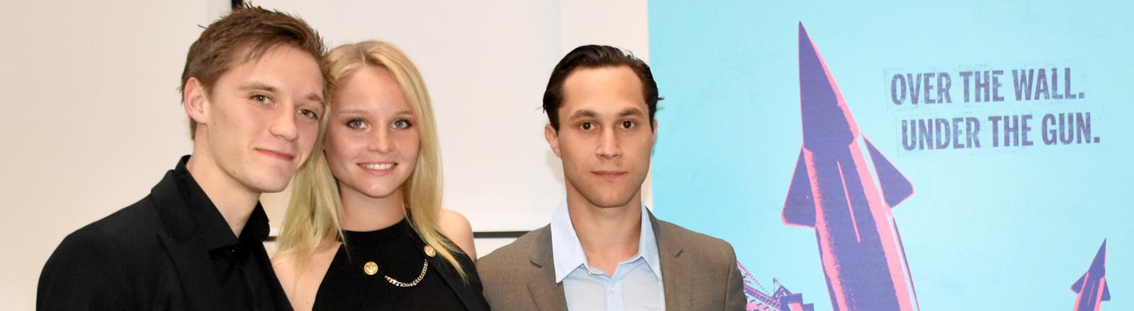 """Die drei Hauptdarsteller der Serie """"Deutschland 83"""", Jonas Nay (l-r), Sonja Gerhardt und Ludwig Trepte stehen am 15.06.2015 in New York vor einem Plakat ihrer Serie."""