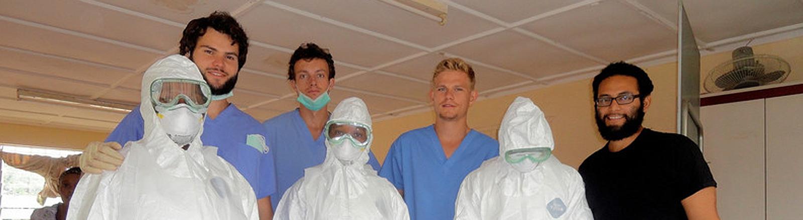 Nicolas Aschoff, Simon Scheiblhuber, Till Eckert und Notfallpfleger Harvey Santos (v.l.) mit drei Krankenschwestern im Sicherheitsanzug