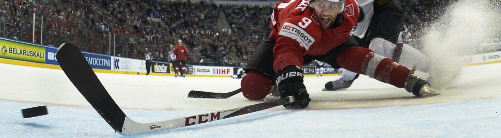 Der Schweizer Spieler Thomas Rufenacht, links und Kristaps Sotnieks aus Lettland kämpfen bei der Eishockey-WM in Weißrussland um den Puck