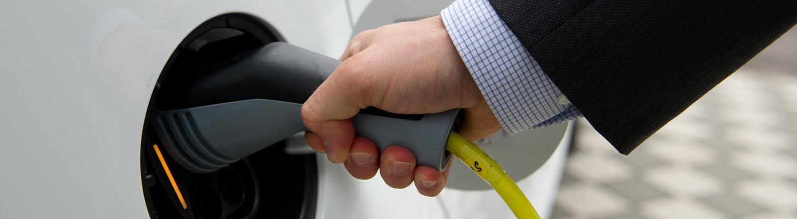 Ein Mann steckt am 04.09.2013 in Wolfsburg (Niedersachsen) ein Ladekabel in einen VW e-Up.